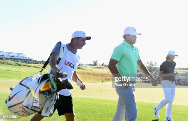 Brooks Koepka of the United States and caddie Richard Elliott walk off the course after finishing during the final round of the 2017 US Open at Erin...
