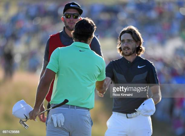 Brooks Koepka of the United States and Tommy Fleetwood of England shake hands after finishing on the 18th green during the final round of the 2017 US...