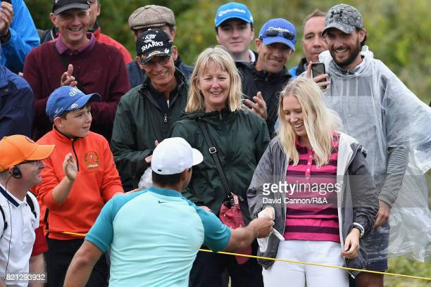Brooks Koepka of the United States gives a fan a signed glove after his ball hit her during the final round of the 146th Open Championship at Royal...