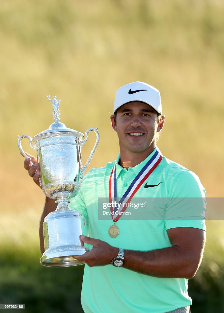 Brooks Koepka of the United States holds the U.S.Open trophy wearing the Jack Nicklaus medal after his four shot win in the final round of the 117th US Open Championship at Erin Hills on June 18, 2017 in Hartford, Wisconsin.