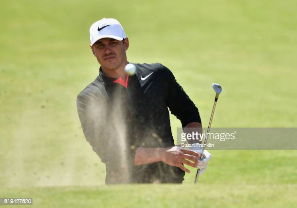 Brooks Koepka of the United States holes his third shot from the bunker on the 17th hole during the first round of the 146th Open Championship at...