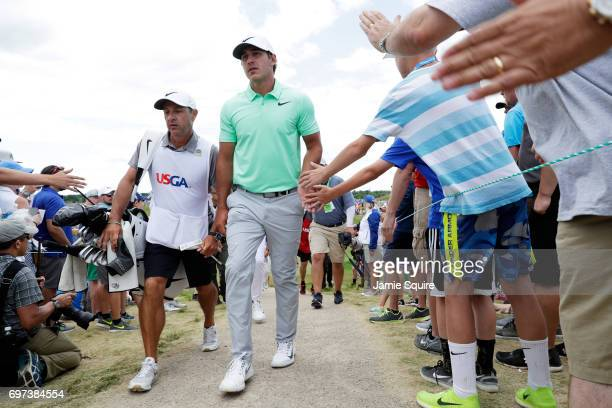Brooks Koepka of the United States interacts with fans while walking to the sixth tee during the final round of the 2017 US Open at Erin Hills on...