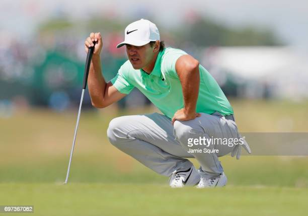 Brooks Koepka of the United States lines up a putt on the first green during the final round of the 2017 US Open at Erin Hills on June 18 2017 in...