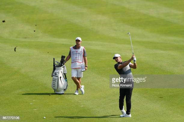 Brooks Koepka of the United States plays a shot on the third hole as caddie Ricky Elliot looks on during the third round of the WGC HSBC Champions at...