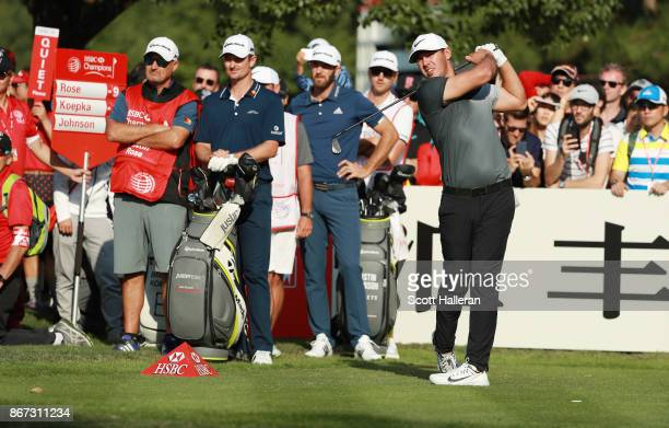 Brooks Koepka of the United States plays his shot from the 15th tee as Dustin Johnson of the United States and Justin Rose of England look on during...