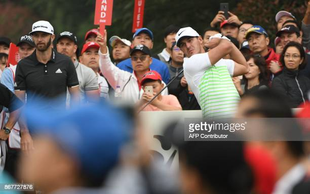 Brooks Koepka of the US tees off as Dustin Johnson o the US watches on during the final round of the 975 million USD WGCHSBC Champions at the Sheshan...