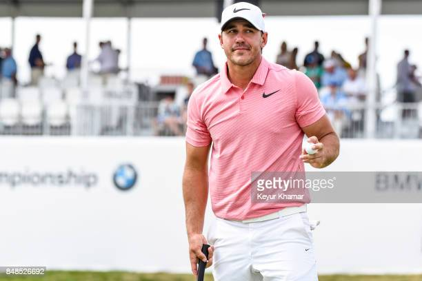 Brooks Koepka waves his ball to fans after making a birdie putt on the 18th hole green during the final round of the BMW Championship at Conway Farms...