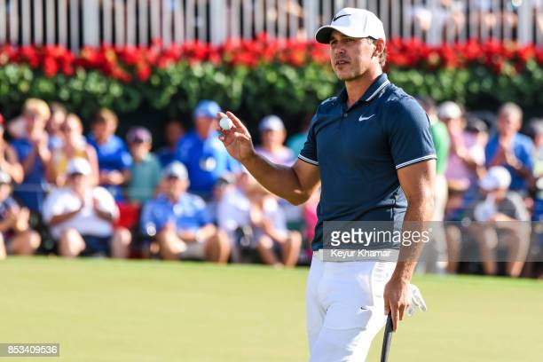 Brooks Koepka waves his ball to fans on the 18th hole green during the final round of the TOUR Championship the last event of the FedExCup Playoffs...