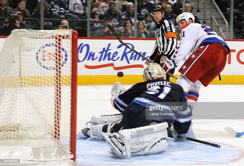 <a gi-track='captionPersonalityLinkClicked' href=/galleries/search?phrase=Brooks+Laich&family=editorial&specificpeople=554432 ng-click='$event.stopPropagation()'>Brooks Laich</a> #21 of the Washington Capitals backhands a shot towards the goal as goaltender Ondrej Pavelec #31 of the Winnipeg Jets stretches his glove out to make the save during third-period action at the MTS Centre on March 21, 2013 in Winnipeg, Manitoba, Canada.