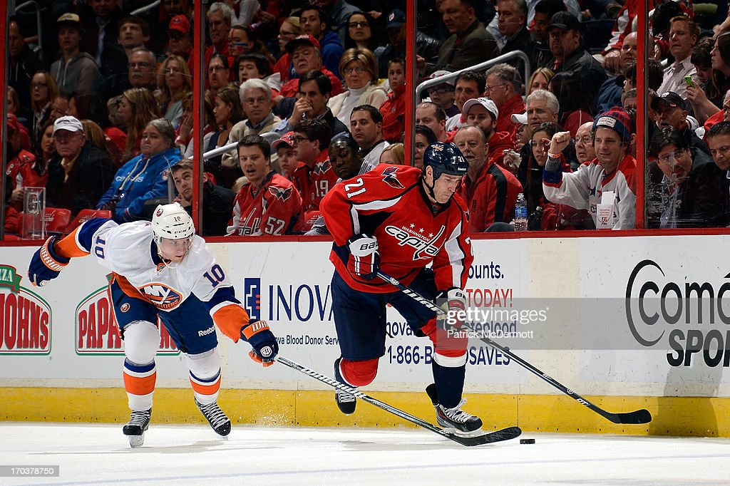 Brooks Laich #21 of the Washington Capitals battles for the puck against Keith Aucoin #10 of the New York Islanders during an NHL game at Verizon Center on April 4, 2013 in Washington, DC.