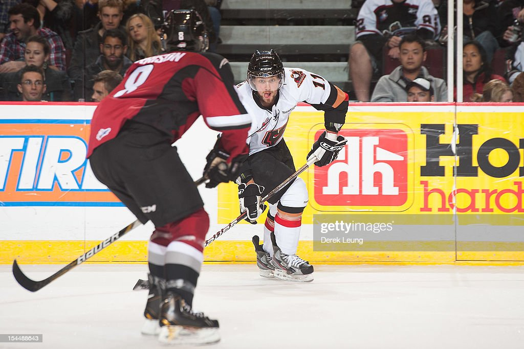 Brooks Macek #11 of the Calgary Hitmen skates against Tyler Morrison #8 of the Vancouver Giants in WHL action on October 20, 2012 at Pacific Coliseum in Vancouver, British Columbia, Canada.