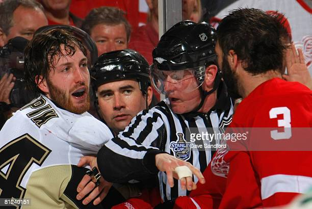 Brooks Orpik of the Pittsburgh Penguins and Andreas Lilja of the Detroit Red Wings are separated by referee Brad Watson and linesman Jean Morin...
