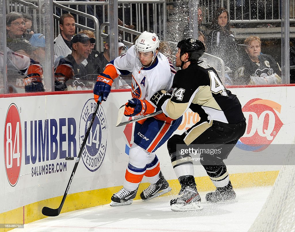 Brooks Orpik #44 of the Pittsburgh Penguins battles for the loos puck against John Tavares #91 of the New York Islanders on March 10, 2013 at Consol Energy Center in Pittsburgh, Pennsylvania. Pittsburgh won the game 6-1.