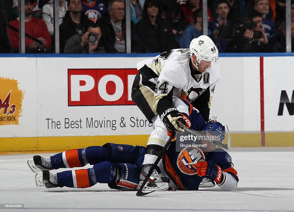 Brooks Orpik #44 of the Pittsburgh Penguins hits Lubomir Visnovsky #11 of the New York Islanders at the Nassau Veterans Memorial Coliseum on March 22, 2013 in Uniondale, New York.