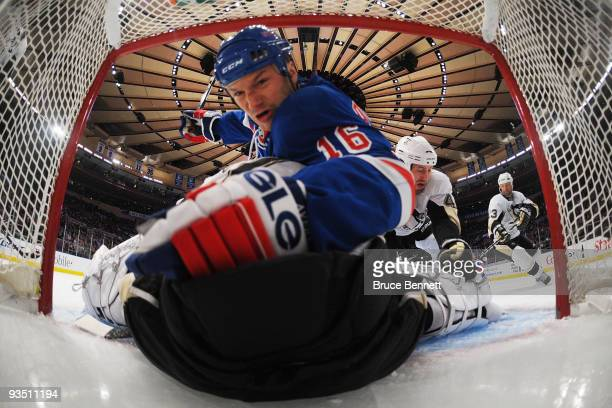 Brooks Orpik of the Pittsburgh Penguins propels Sean Avery of the New York Rangers over goaltender MarcAndre Fleury at Madison Square Garden on...