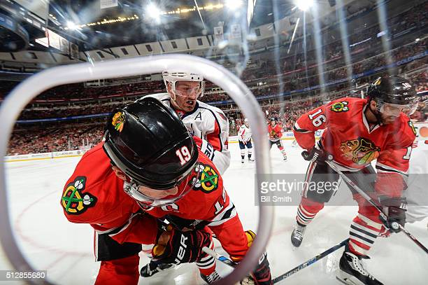 Brooks Orpik of the Washington Capitals chases the puck against Jonathan Toews and Andrew Ladd of the Chicago Blackhawks in the first period of the...