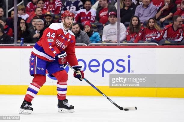 Brooks Orpik of the Washington Capitals controls the puck against the Detroit Red Wings in the first period during an NHL game at Verizon Center on...