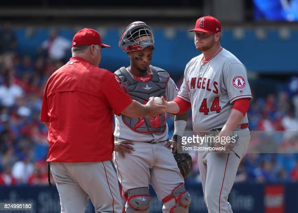 Brooks Pounders of the Los Angeles Angels of Anaheim gives the ball up to manager Mike Scioscia as he is relieved while Martin Maldonado looks on in...