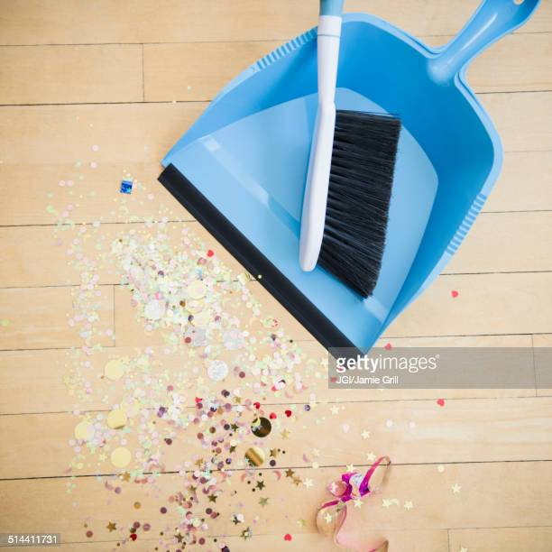 Broom and dustpan with confetti on floor