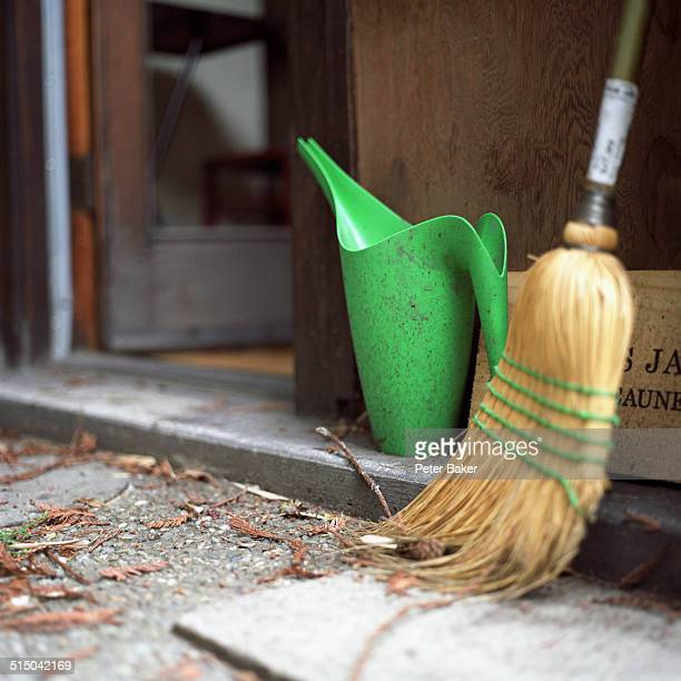 A broom and watering can outside a doorway, close-up