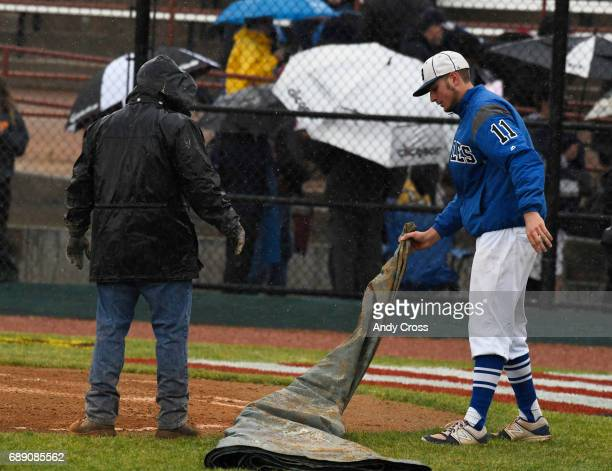 Broomfield Eagles pitcher James Notary right helps a grounds crew member with a tarp to cover home plate during a heavy rain storm after Colorado...