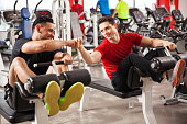 Two athletic young man bumping their fists as a sign of friendship and working out together at a gym
