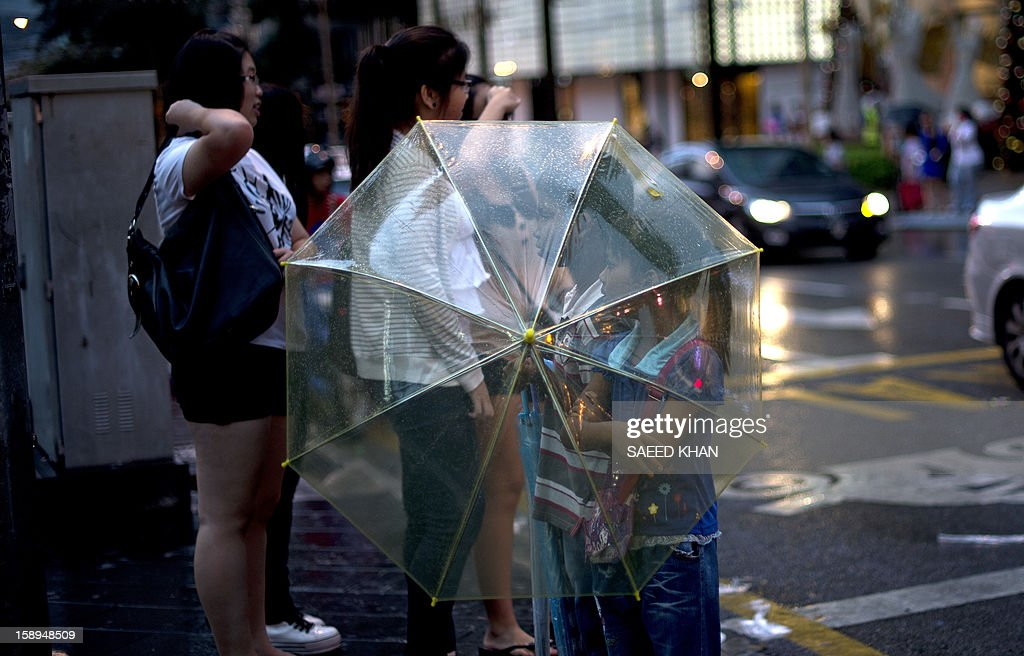 A brother and his sister sell umbrellas during a light rain outside a shopping mall in downtown Kuala Lumpur on January 4, 2013. Malaysia is heavily reliant on migrant workers: they number about 2.2 million people and are the mainstays of the plantation and manufacturing sectors. AFP PHOTO / Saeed Khan