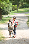 Brother and little sister walking a path with hand in hand, summer
