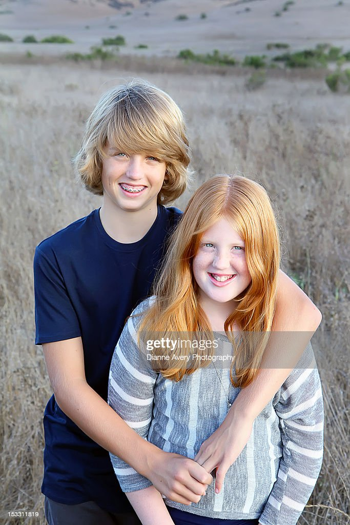 Brother and red haired sister in dry grass field : Stock Photo