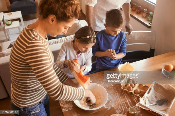 brother and sister assisting their mother with baking