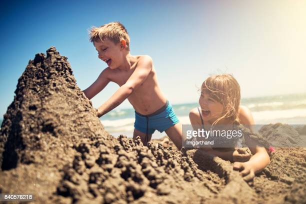 Brother and sister building a sandcastle on beach