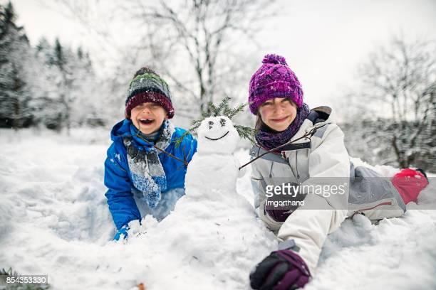 Bruder und Schwester beim Schneemannbauen an einem Wintertag