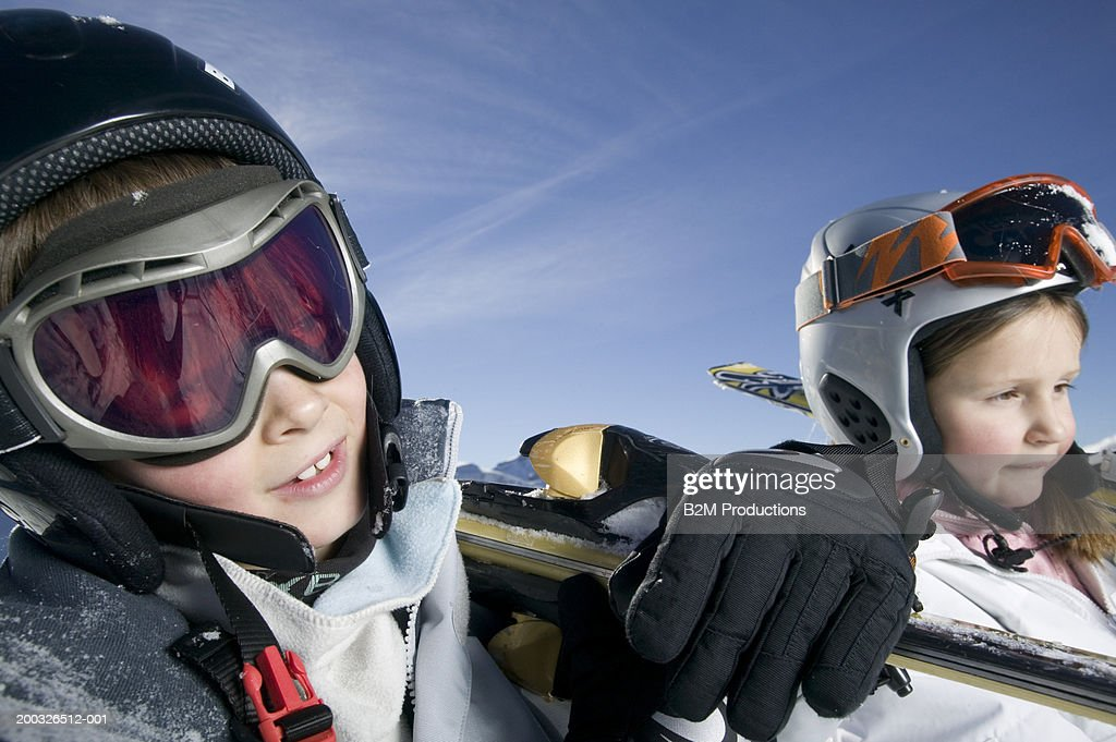Brother and sister (7-9) carrying  skis on shoulders, close-up : Stock Photo