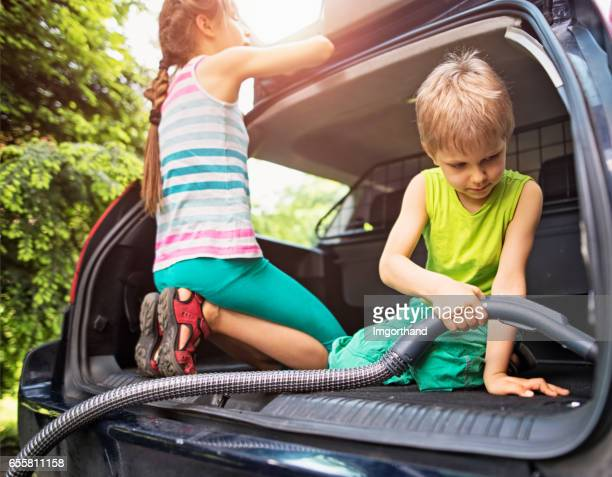 Brother and sister cleaning family car interior