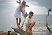 Brother and Sister Climb Large Drift Wood on Beach