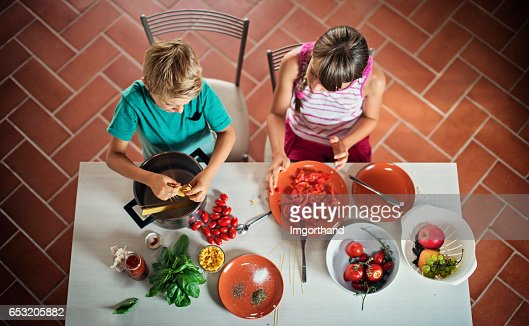 Brother and sister cooking spaghetti for dinner. : Stock Photo