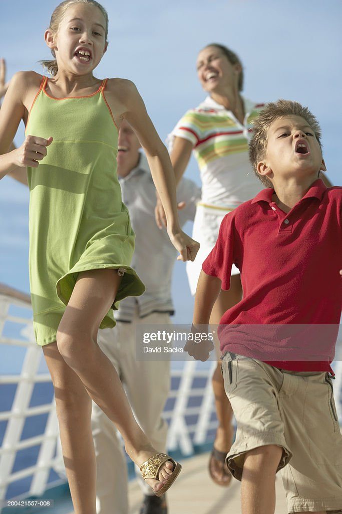 Brother and sister (10-12) dancing on cruise ship, with parents : Stock Photo