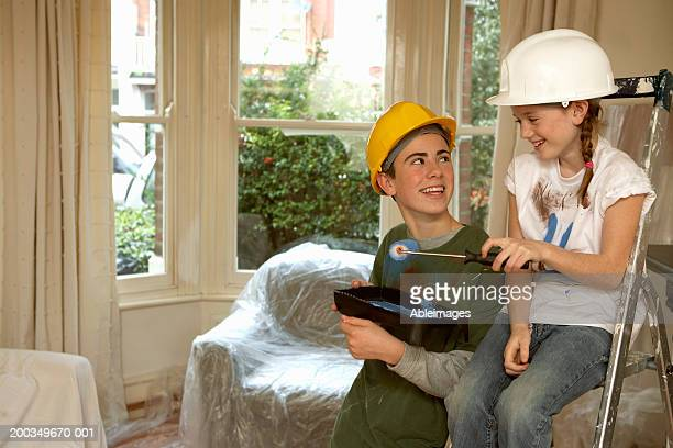Brother and sister (8-14) decorating room, wearing hardhats