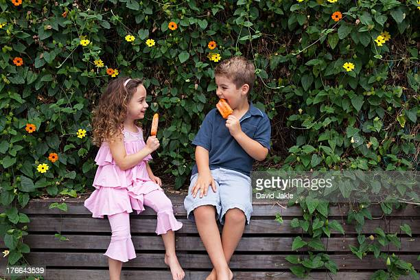 Brother and sister eating ice lollies by plants