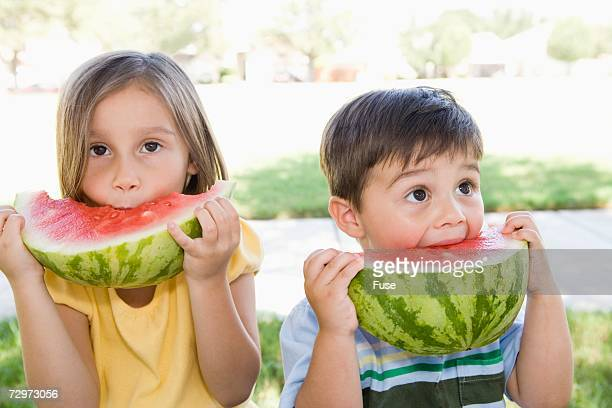 Brother and sister eating watermelon