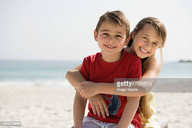 Brother and sister embracing on a beach
