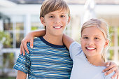 Cheerful young brother and sister embracing each other. Cute children smiling and looking at camera. Portrait of happy young boy and little girl hugging.