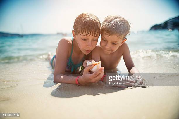 Brother and sister examining sea shells