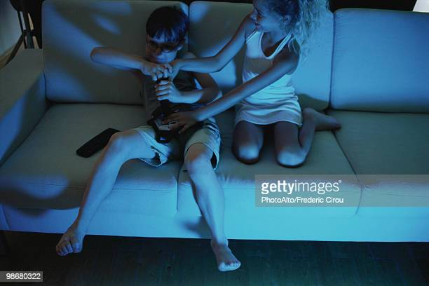 Brother and sister fighting over video game controller on sofa