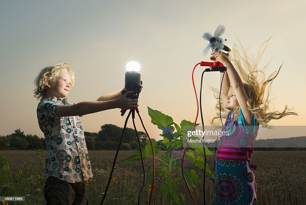 Brother and sister generating light from wind power, Zeeland, Netherlands : Foto stock