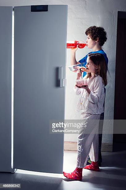 Brother and Sister Getting Late Night Snacks From The Fridge.