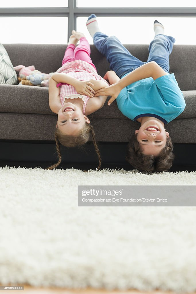 Brother and sister hanging upside down on sofa : Stock Photo