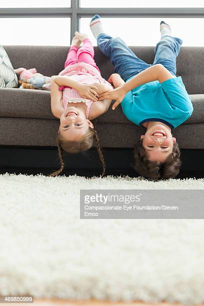 Brother and sister hanging upside down on sofa