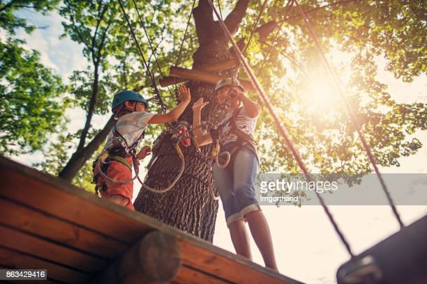 Brother and sister having fun during in ropes course  adventure park