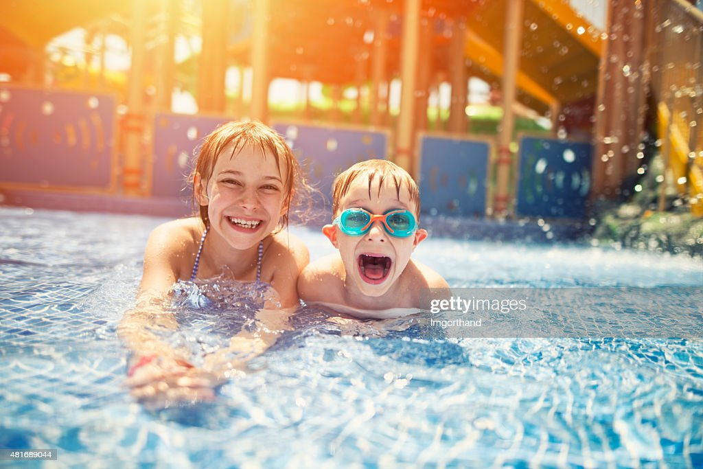 Brother and sister having fun in water park : Stock Photo